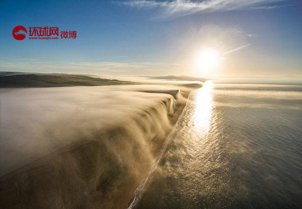 """英国摄影师詹姆斯•洛夫里奇位在多塞特郡的西湾悬崖处,使用无人机拍摄下了清晨由于""""逆温现象""""形成的壮丽景象——笼罩在悬崖周围的雾气,如瀑布般奔腾而下,美得令人窒息。"""